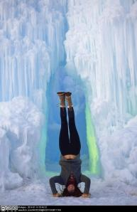 Picture of someone doing a headstand in front of a frozen waterfall