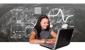 Women using a laptop, with chalkboard behind