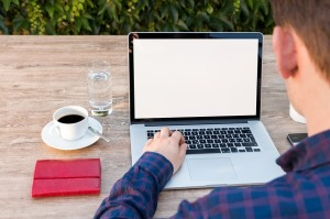Image of someone working on a computer outside on a bench with a cup of coffee