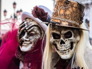 Image of 2 carnival goes wearing skeleton masks and hats. The image is rectangular with a hard border.