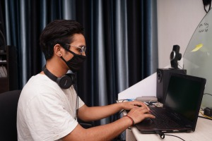 Image of a learner working at a laptop whilst wearing a mask