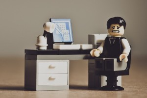 Lego person sat a desk with computer station set up